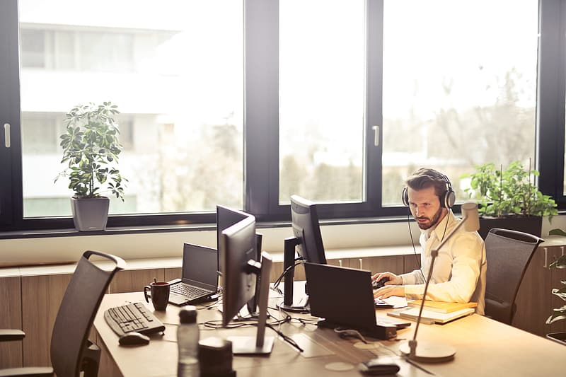 Young Adult Man in white shirt, working at computer while listening music with headphones