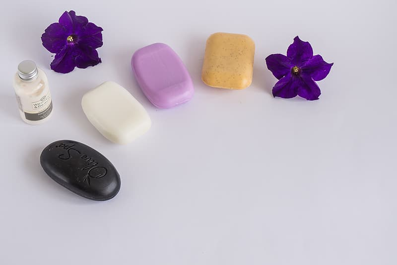 Four assorted-color soaps on white surface