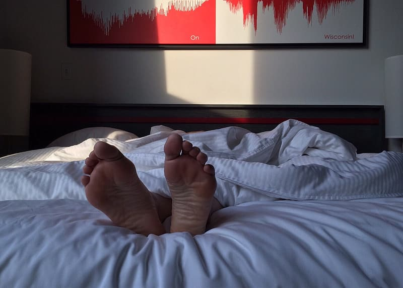 Person in white pants lying on bed