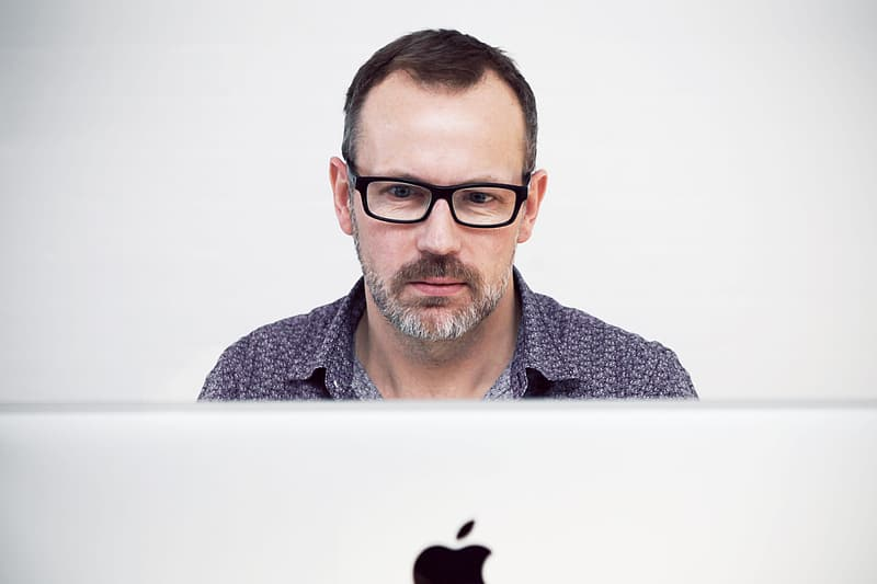 Man in black button-top in front of iMac