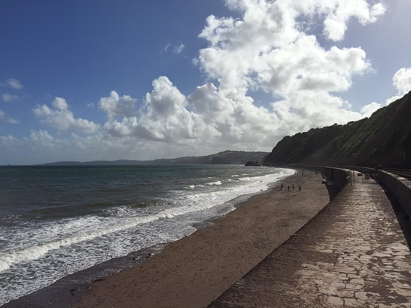 Brown sand beach near green mountain under blue and white sunny cloudy sky during daytime