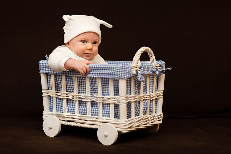 Baby wearing white cap riding bassinet