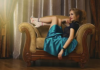 Woman in blue skirt sitting on brown chair