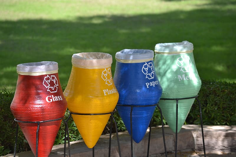 Four assorted-color garbage pots near green grass field