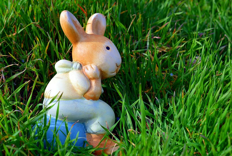 Brown, white, and blue ceramic rabbit figurine on green grass at daytime