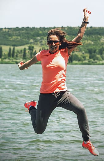 Photo of woman jumping near body of water during daytime