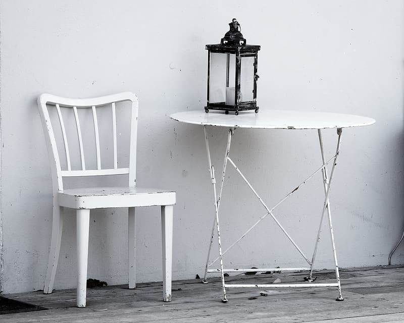 White wooden chair beside round table
