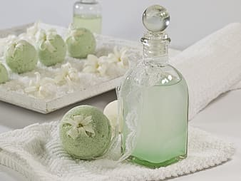 Clear glass bottle beside green cake pops placed on white knitted textile