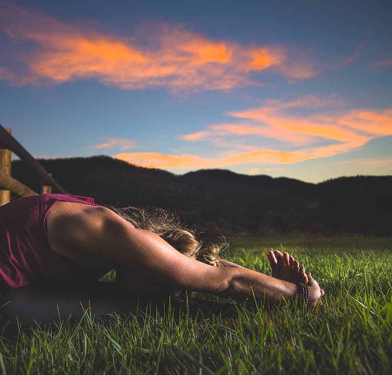 Woman sitting on grass doing stretching