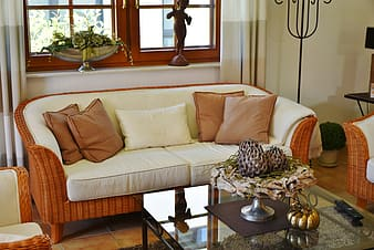 Brown wicker couch with white cushions and throw pillows