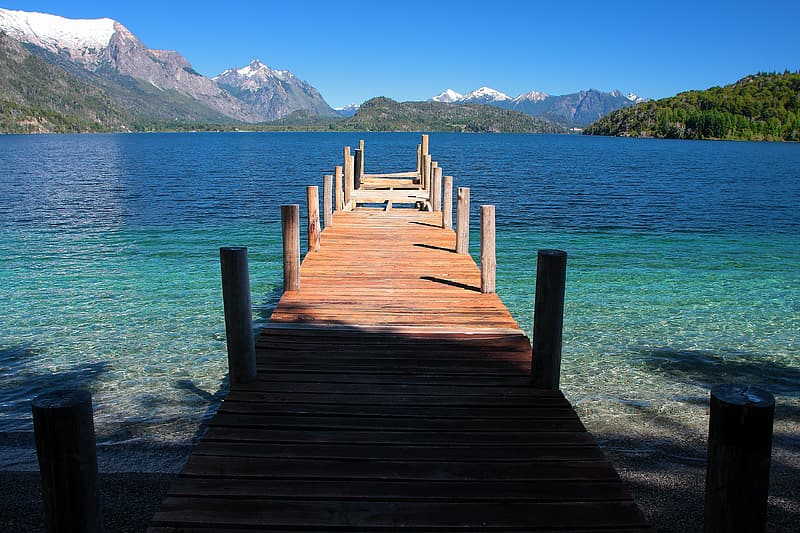Brown wooden pier on body of water