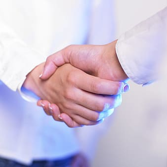 Person in white dress shirt holding hands of person in white dress shirt