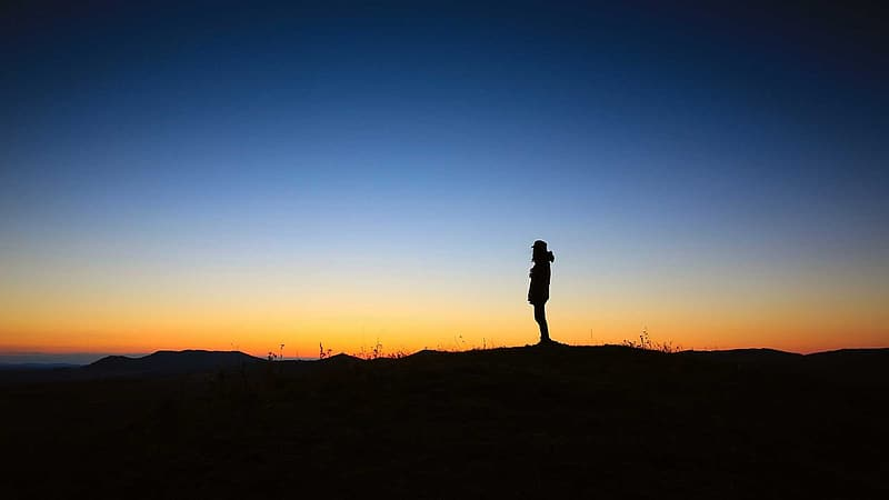 Silhouette of person standing on the cliff