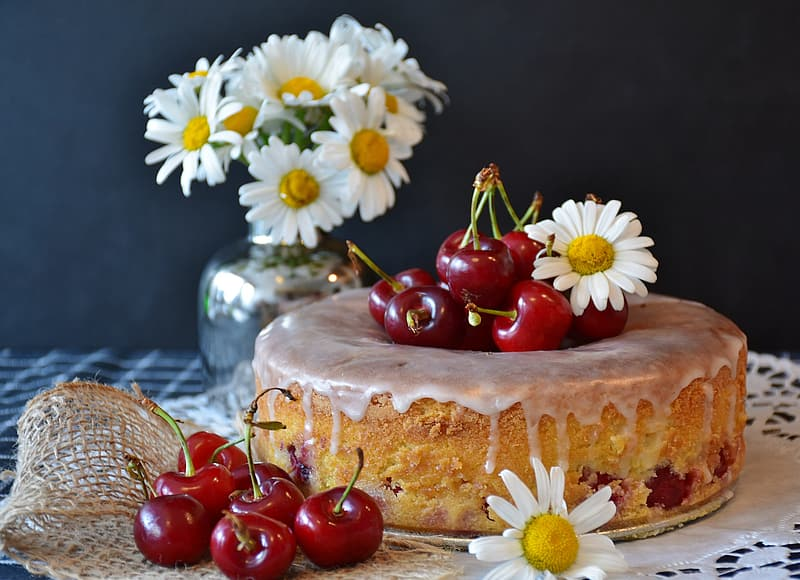 Cherry fruits and white flowers on table