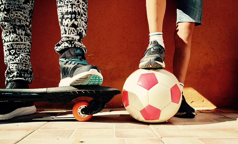 White and red soccer ball beside black skateboard