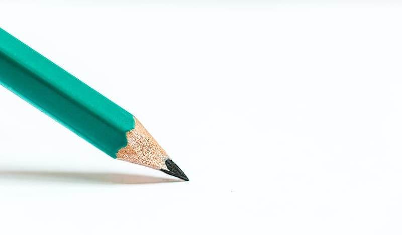 Green pencil on top of white paper