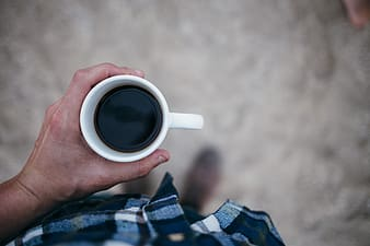 Person holding black coffee filled white ceramic mug