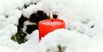 Lighted red pillar candle near white snow