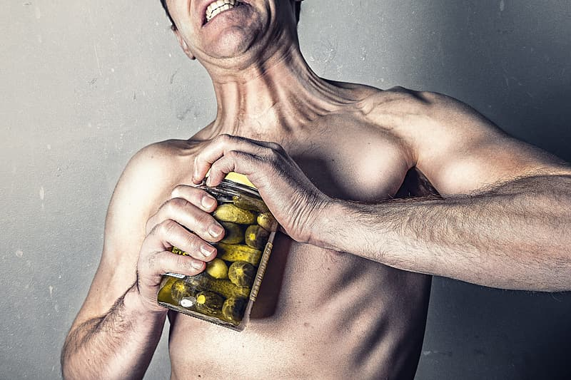 Topless man holding jar of green and yellow fruits