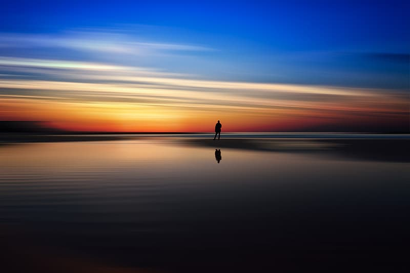 Silhouette of man near body of water during sunset