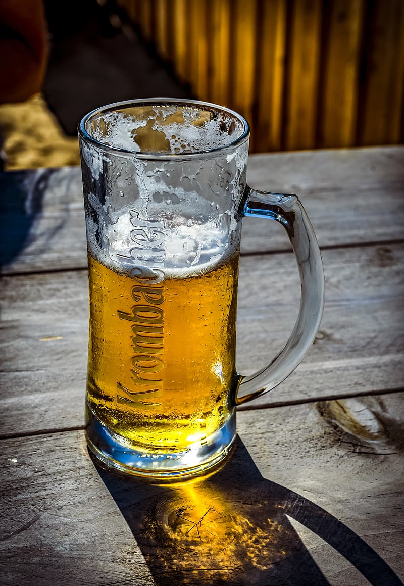 Clear glass beer mug on brown wooden table