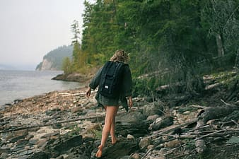 Person wearing green dress shirt walking on rocky seashore