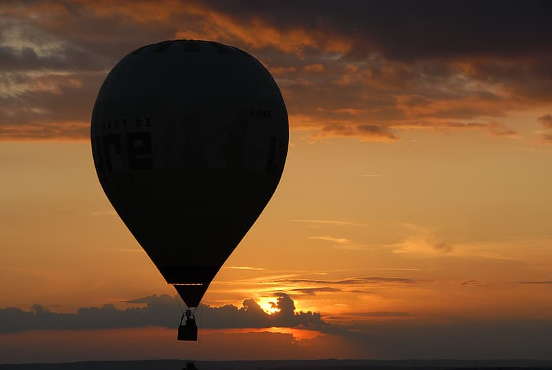 Person riding hot air balloon during golden hour
