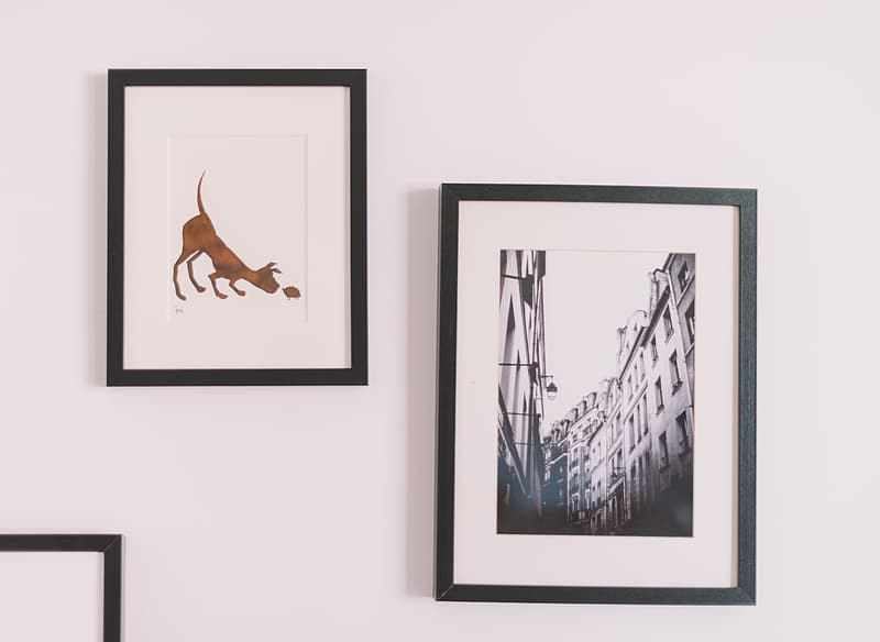 Two black framed paintings on wall