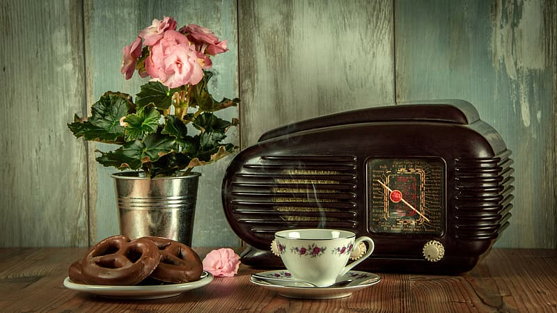 Black vintage radio and white ceramic cup with saucer on brown surface