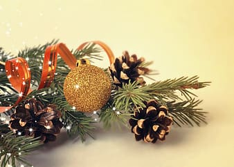 Closeup photo of a gold bauble hanging on lit tree