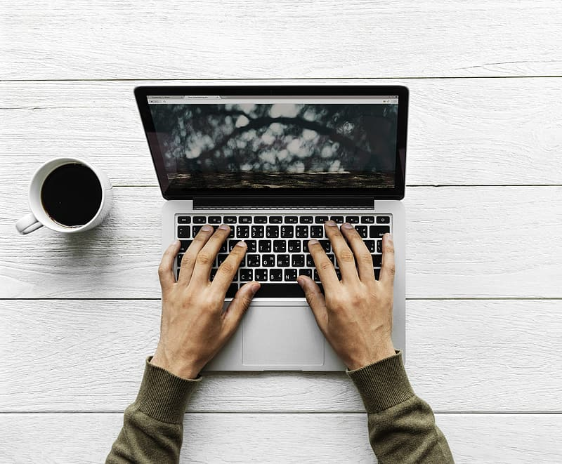Person in front of MacBook Pro on table beside white ceramic mug