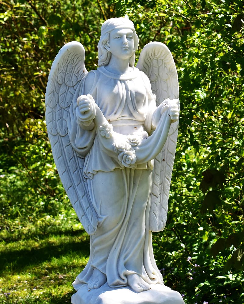 White angel statue near green trees during daytime