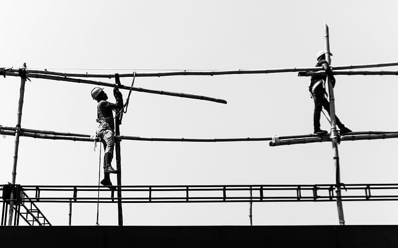 Two men on scaffolding under sunny sky