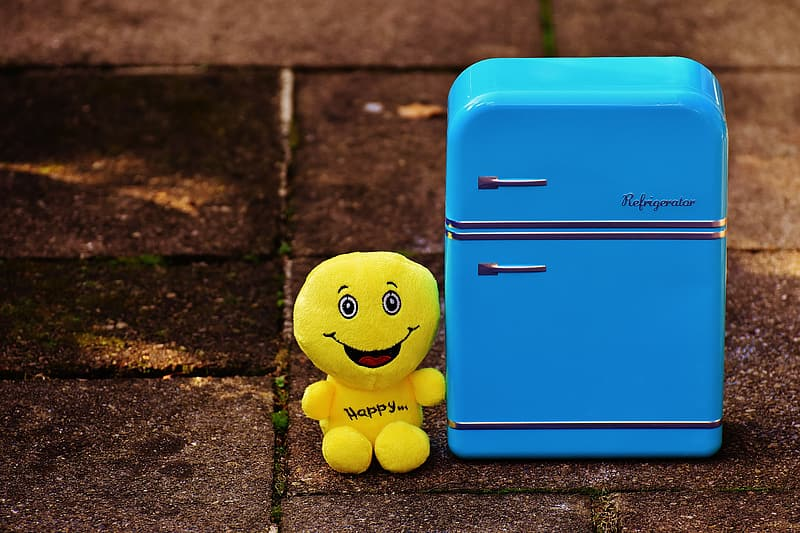 Yellow smiley plush toy on blue plastic container