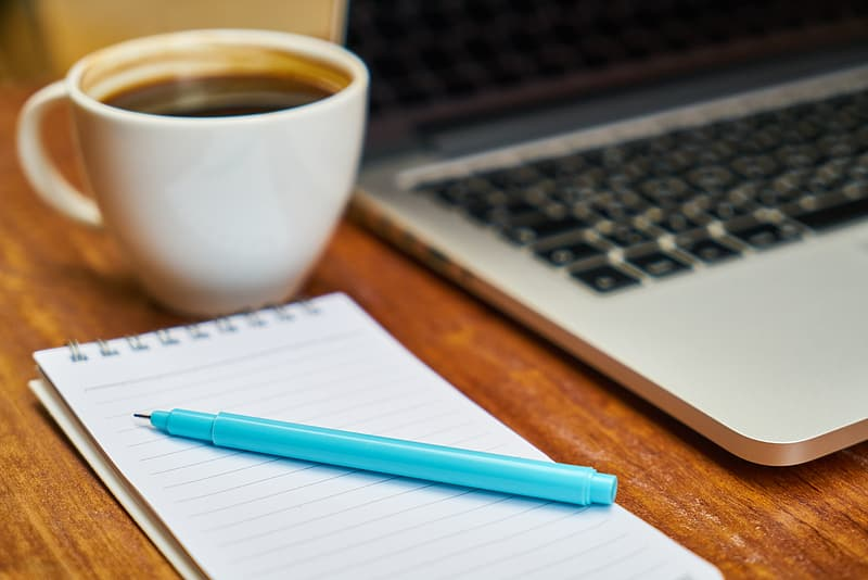 Shallow focus photography of blue pen on top of white notepad beside a white ceramic cup filled with coffee and gray laptop computer