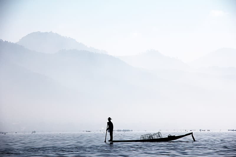 Silhouette of man standing on boat near mountain