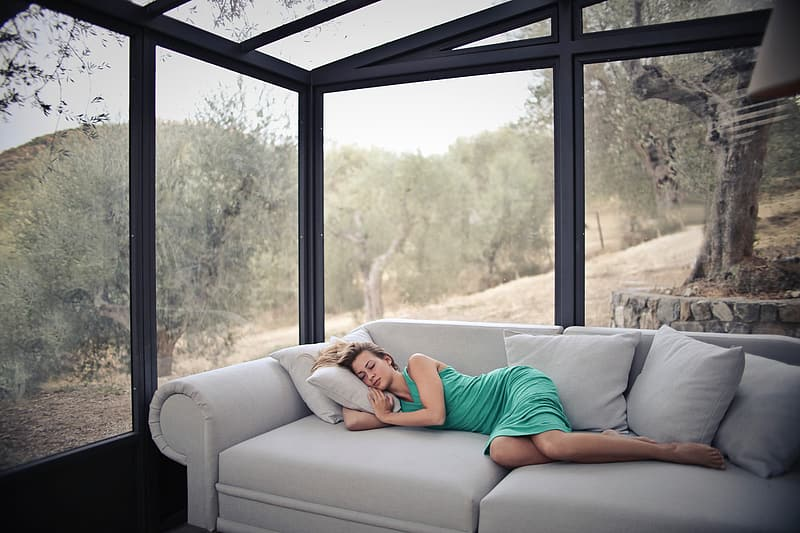 A young blonde woman sleeping on the couch in a glass house in the woods |  Pikrepo