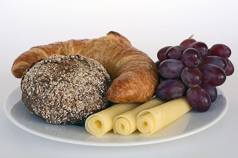 Purple grapes with croissant and roll cheese on plate