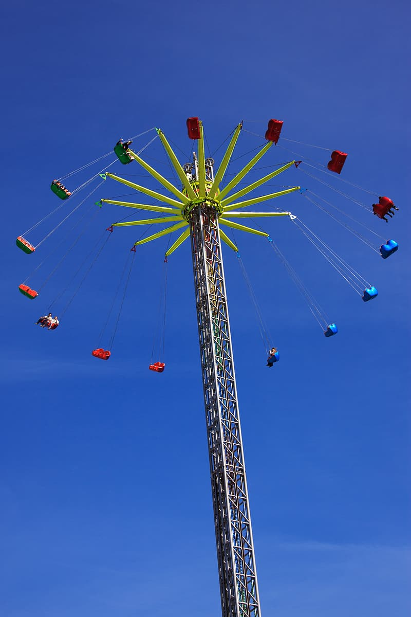Yellow and red ferris wheel under blue sky during daytime