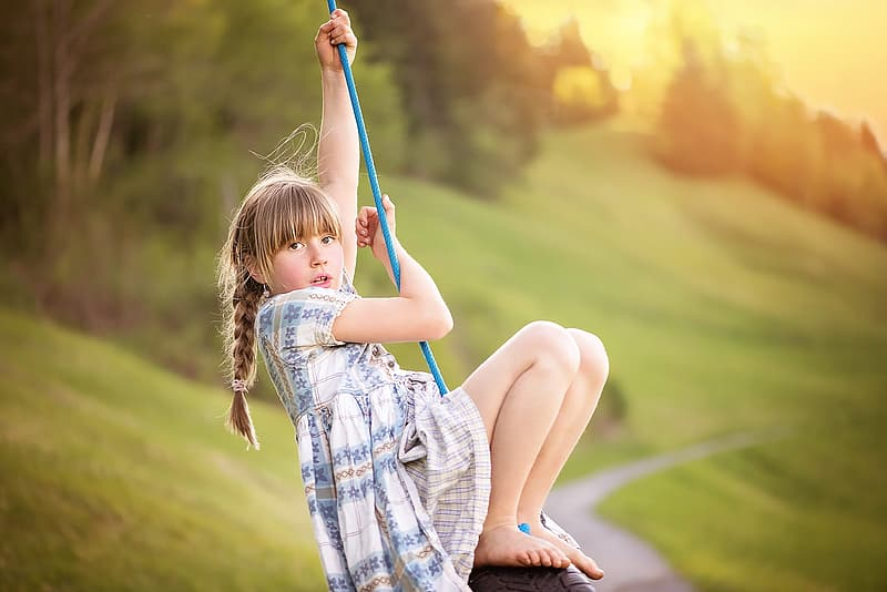 Girl sitting on swing holding rope during day