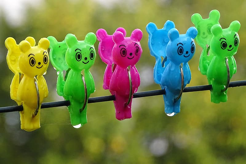 Closed photography of five assorted-color bear clothes clips on cable