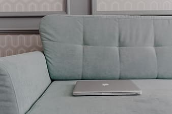 MacBook laptop lying on mint couch