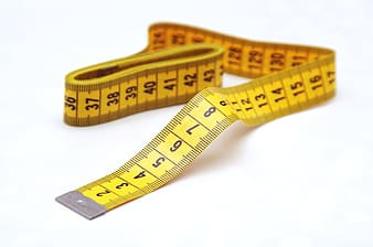 View of yellow tape measure on white surface