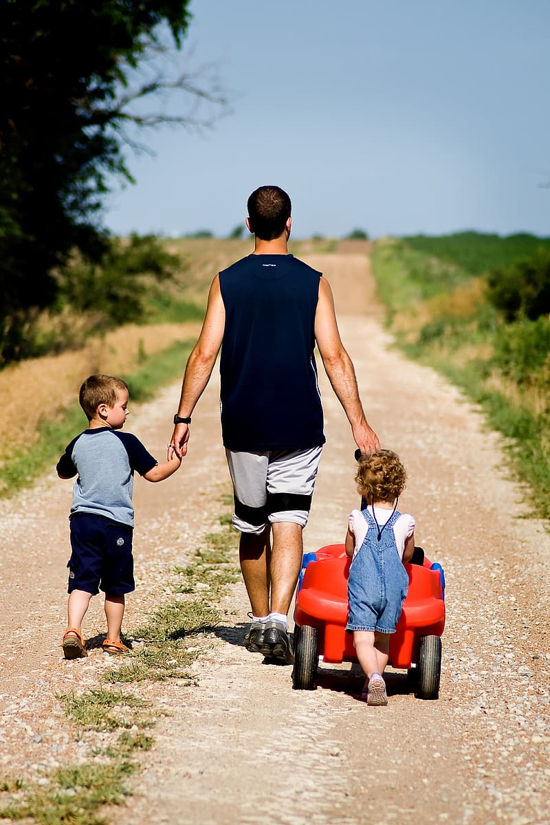 Man walking with two children on brown road
