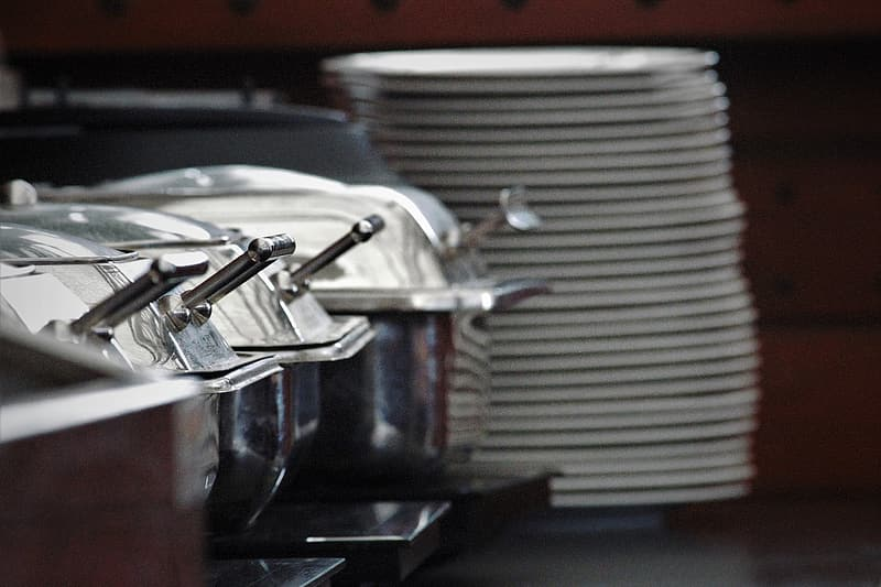 Grey stainless steel buffet server near stack of white ceramic plates