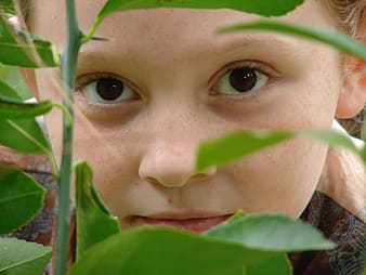 Closeup photo of girl face beside green leaves