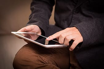 Person wearing black dress shirt and brown pants holding white ipad