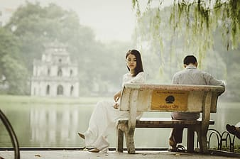 Woman sitting on bench near bodies of water photograph