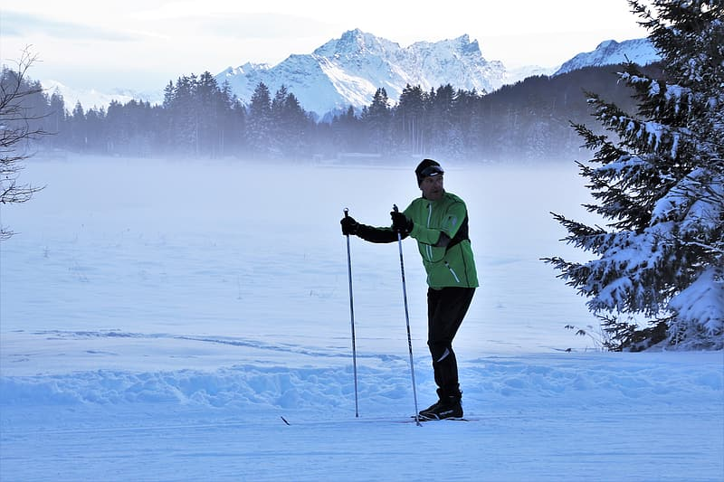 Man in green jacket and black pants standing on snow covered ground during daytime