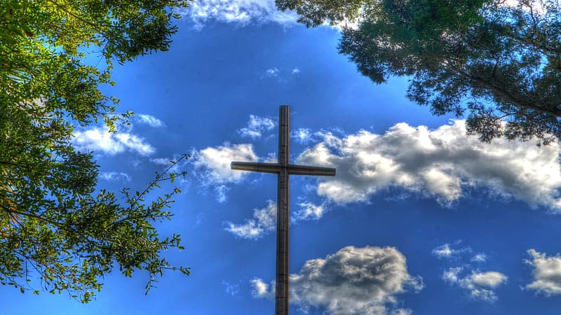 Brown wooden cross under the blue sky